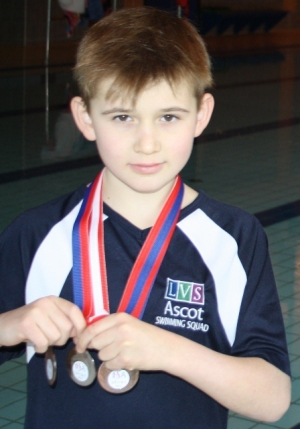 Archie Gardiner with his three medals at the LVS Ascot school swimming pool